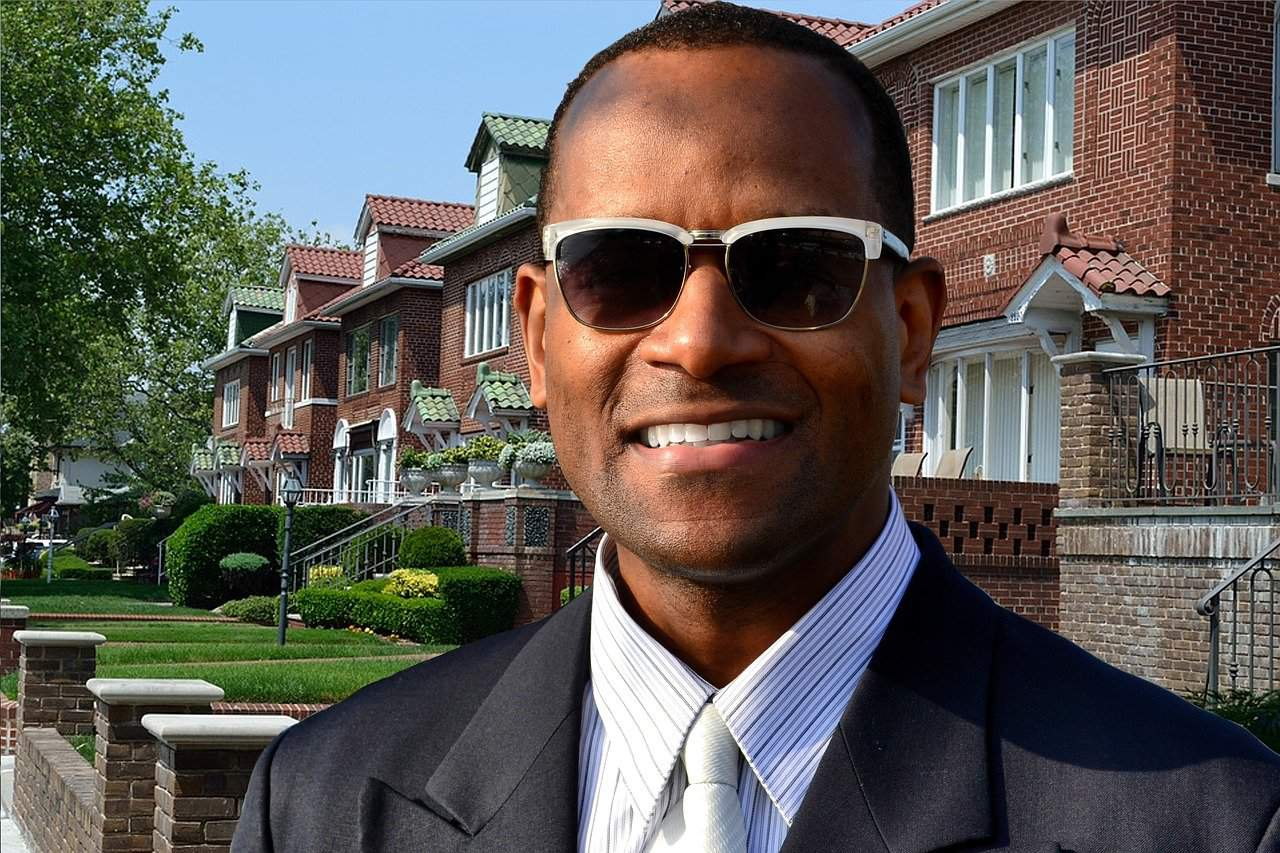 A man wearing a suit and sunglasses in front of a building